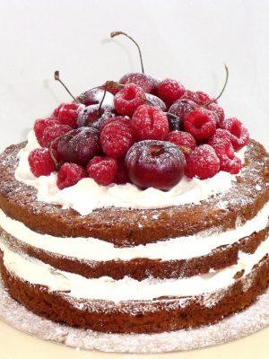 tarta con bizcochos desnudos rellenos de buttercream, adornada con frutas naturales