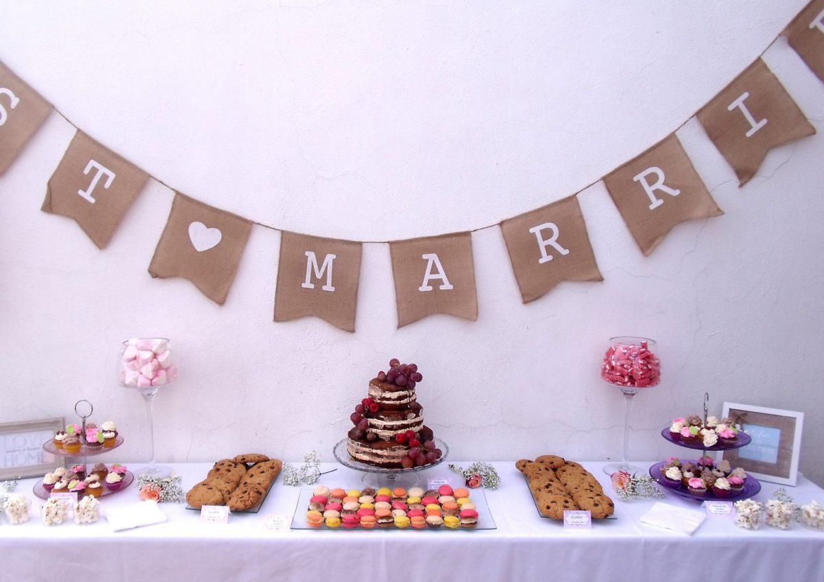 Mesa dulce con tarta desnuda decorada con frutos rojos, gominolas, mini Cupcakes, macarons y galletas con chispas de chocolate