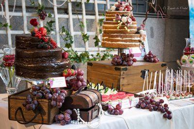 Tarta desnuda de tres pisos decorada con flores y frutos rojos, tarta de tres pisos cubiertos de chocolate negro decorada con frutos rojos, cupcakes, galletas tipo piruleta y cake pops