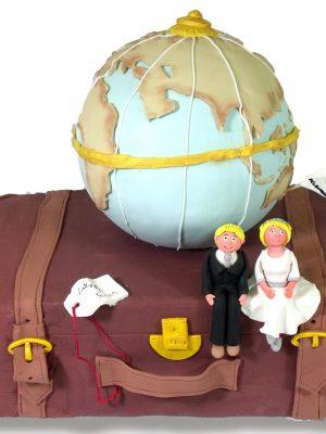tarta rectangular con forma de maleta, decorada con una bola del mundo y dos figuras de novios sentados encima de la maleta