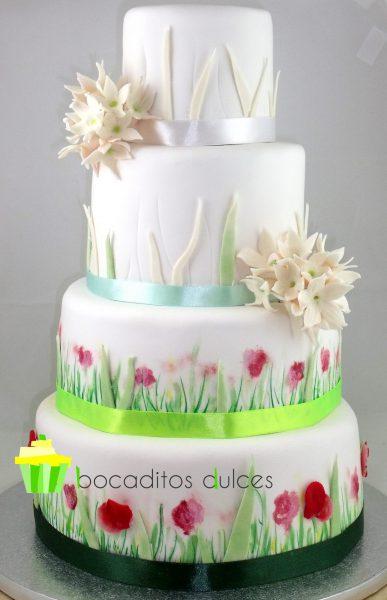 Tarta de cuatro pisos decorada con flores pintadas a mano y otras echas de fondant