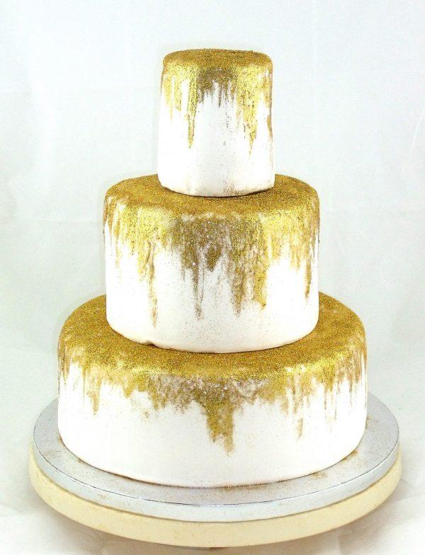 Tarta de tres pisos cubierta de fondant blanco y pintada con un tono dorado.