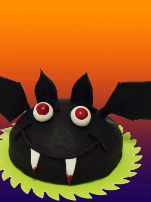 Tarta con forma redondeada cubierta de fondant negro dando forma al cuerpo de un murciélago y unas alas de fondant negro colocadas a cada lado de la tarta.