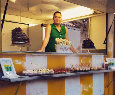 Mesa dulce compuesta por dos tartar desnudas decoradas con frutas del bosque, cupckes de vaililla, cake pops, galletas piruleta decoradas con papel de azúcar y mini postres en vasitos