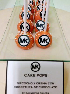 Cake pops son bolitas de bizcocho insertados en un palo de chupa chups, cubiertos de cholocales de color naranja y unas bolitas blancas y el logo de la empresa en su frontal realizado con papel de azúcar.