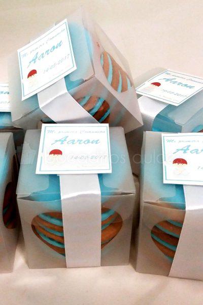 Caja de plastico con cinco galletas de mantequilla decoradas con fondant azul y en su extrior va decorada con etiqueta personalizada.