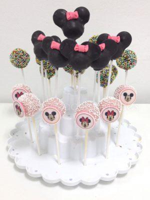 Bola de bizcocho cubierta de chocolate de colores inserado en un palo de chupa chups , unos con virutas de colores y otras con semicirculos negras de fondant a modo de orejas de Minnie Mouse y un lazo de color rosa.
