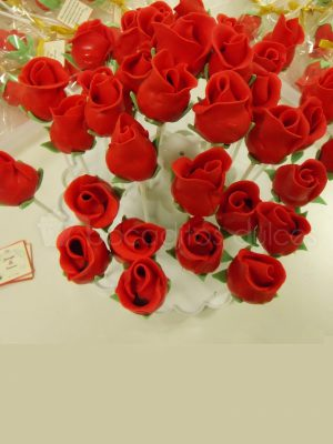 Bola de bizcocho, insertada en un palo de chupa chups, bañado en chocolate y decorado con fondant rojo en forma de rosa.
