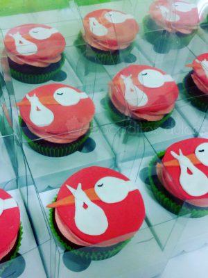 Cupcakes de chocolate, decorados con buttercream de fresa y un circulo fucsia de fondant el cual esta decorado a su vez por una cigüeña de fondan que sostiene una bolsita en su pico.
