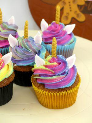 Cupcakes de chocolate, decorado con una buttercream de diferntes colores y a su vez con unas orejitas y un cuerno que hacen que parezca un Unicornio.