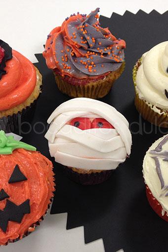 Cupcakes de diferntes sabores y colores decorados con forma de calabaza, fantasma, y momia.