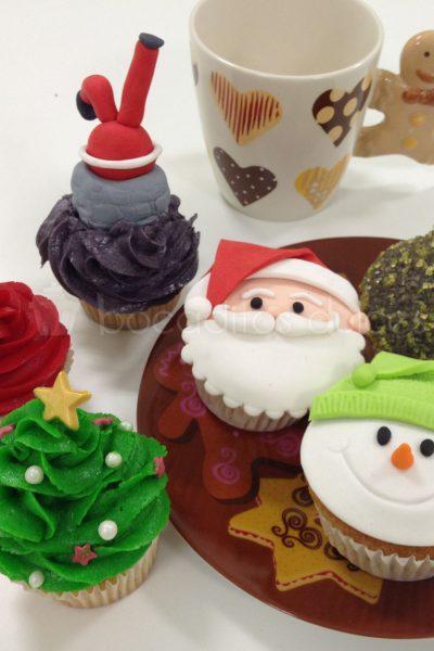 Cupcakes con buttercream de distintos colores, decorados con la cara de papa noel, cara de un muñeco de nieve, papa noel en una pequeña chimenea de fondant y un arbol navideño con buttercream.