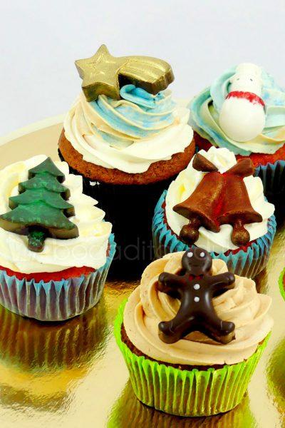 Cupcakes decorados con buttercream de vainilla, y encima pequeñas chocolatinas com arbol de navidad, estrella de oriente, muñeco de nieve, campanas y muñequito de jengibre.