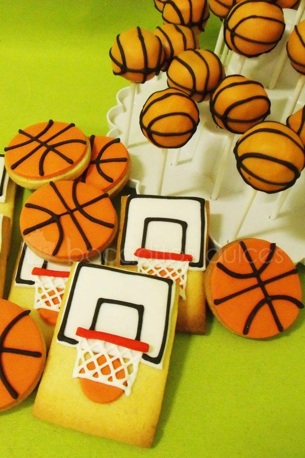 Galletas de mantequilla redondas decoradas con fonant naranja dando forma a un balon de baloncesto, galletas de mantequilla rectangulares decoradas con fondant recreando una canasta de baloncesto.
