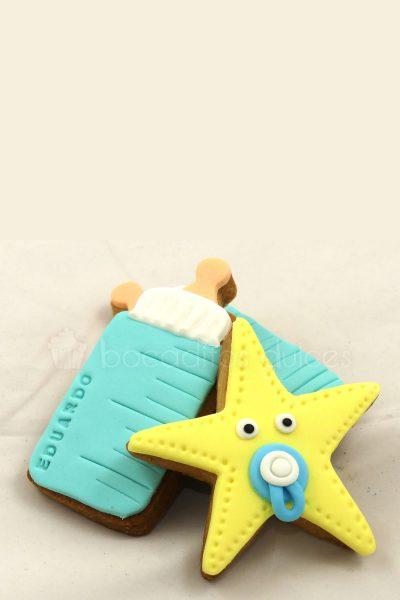 Galletas de mantequilla con forma de estrella decorada con fondant color amarillo, y otra galleta decorada con forma de biberon en fondant azul y blanco.