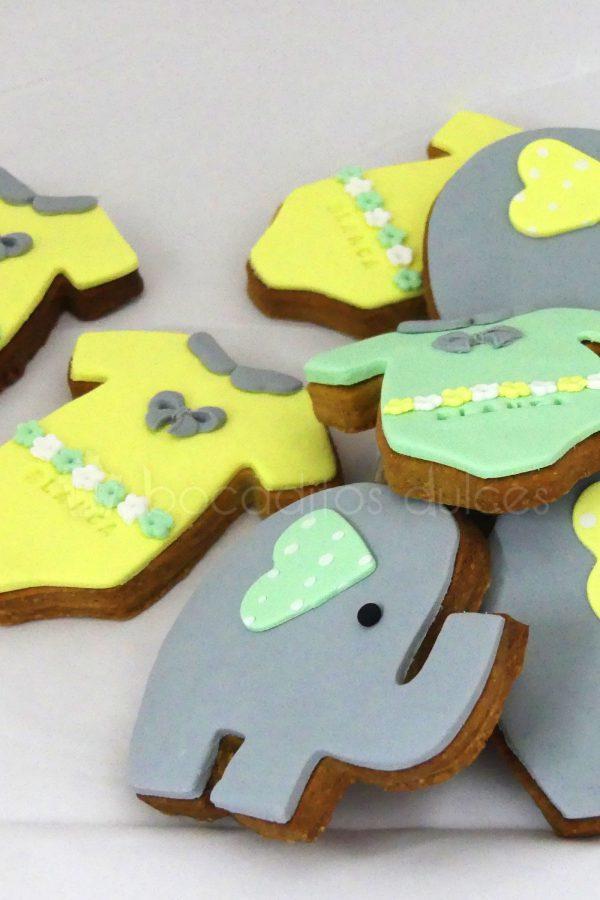 Galletas de mantequilla con forma de body de bebe decorado con fondant amarillo, galletas con forma de elefante decorado con fondant gris.