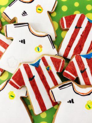Galletas de mantequilla con forma de camiseta decorada con fondant y la camiseta del Real Madrid cub de Futbol y otra galleta decorada en fondant con la camiseta del Atletico de Madrid.