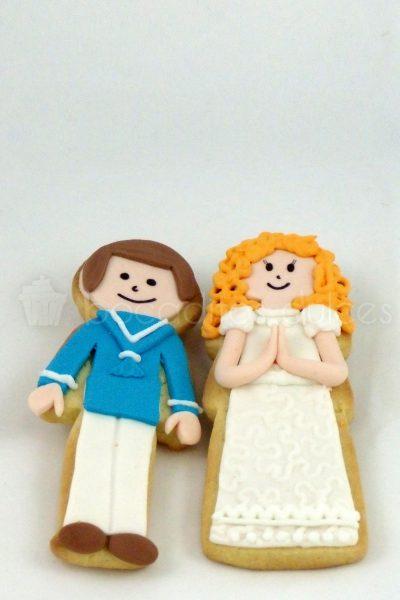 Galletas de mantequilla con forma de niño o niña vestidos con traje de comunión en fondant.