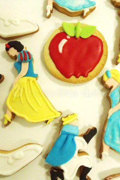 Galletas de mantequilla decoradas con glaseado real en forma de manzana, galleta de cenicienta decorada con galaseado real, galleta de blancanieves decorada con glaseado real y galleta de principe decorada con glasa real.