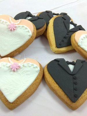 Galletas de mantequilla con forma de corazon decoradas de forma personalizada recreando los trajes de los novios en fondant.