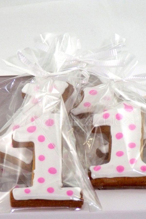 Galleta de mantequilla con forma de número uno decorada con fondant blanco y puntitos rosas.