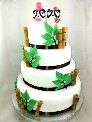 Tarta de cuatro pisos cubiertos de fondant blanco y decorados todos ellos con una cinta negra alrededor, hojas y ramas de bambú