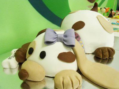 Dos tartas unidas que forman el cuerpo del perrito, cubiertas de fondan blanco y pequeñas manchas de color marron patitias de fondant y en la cabeza lazo de fondant de color morado.