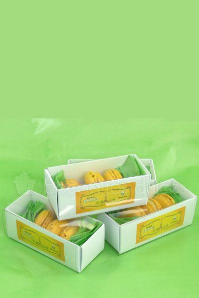 Macarons amarillos de sabor limon en cajita de cuatro unidades con logotipo personalizado.