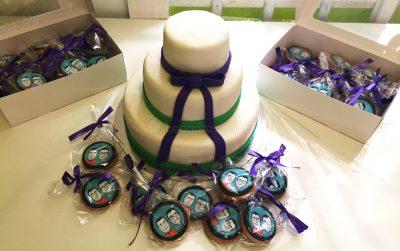 Tarta de tres pisos cubiertos de fondant blanco y decorados con cintas de fondant color verde y lazo en fondant azul, galletas de mantequilla con dibujo personalizado en papel de azúcar enbolsadas individualmente.