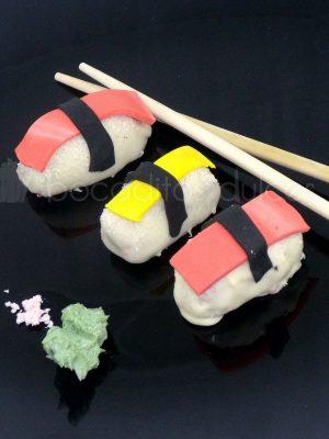 piezas de delicioso nigiri dulce. relleno de bizcocho con cobertura de chocolate y detalles en pasta de azúcar