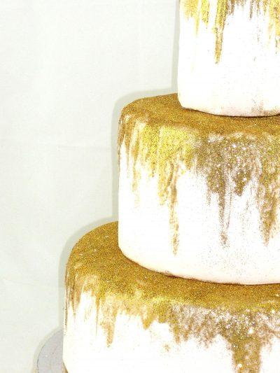 Detalle de tarta blanca de 3 pisos con purpurina dorada