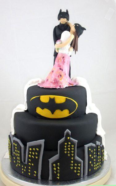 Tarta de tres pisos cubiertos con fondant negra y decoraciones sobre batman en fondant y en el piso superios dos figuras con traje de novios y mascara de batman.