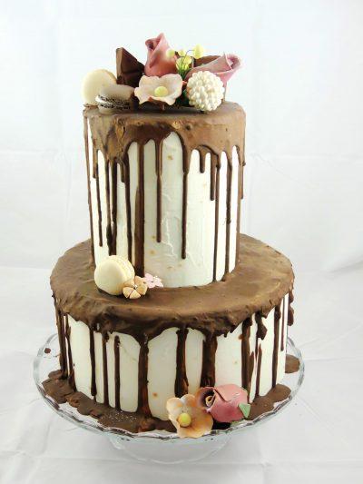 Tarta de dos pisos cubierta de butercream blanco y chocolate negro chorreando y decorada con flores talladas de fondant.