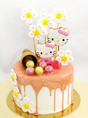 Tarta cubierta de buttercream blanca, con chocolate de fresa chorreando, galletas con la cara de hello kitty, diversas chuches de colores y barquillo de chocolate.