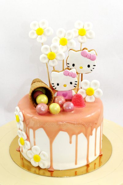 Tarta cubierta de buttercream blanca, con chocolate de fresa chorreando, galletas con la cara de hello kitty, diversas chuches de colores y barquillo de chocolate.