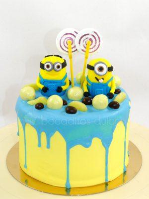 Tarta cubierta de buttercream de color amarillo con chocolate derretido por encima de color azul, decorado con chuches, y dos muñecos de la pelicula minions de fondant.