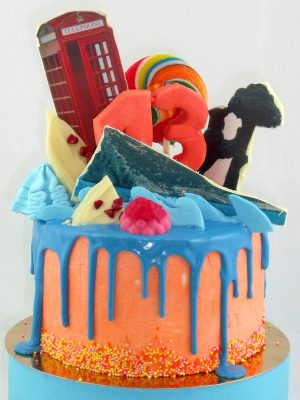 Tarta drip cake cubierta de buttercream rosa y birtas de colores, chocolate azul derretido, y decorado con diferentes tipos de dulces y diferentes temas personalizados.