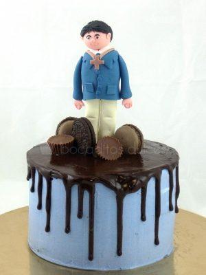 Tarta cubierta de buttercream azul con chocolate negro fundido, decorado con distintos tipos de dulces y un muñeco de cumunion modelado en fondant.