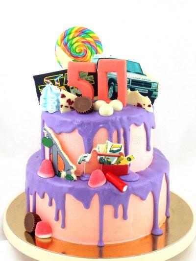 Tarta de tres pisos cubierta de buttercream rosa y chocolate fundido de color morado decorada con distintos tipos de dulces y diferentes figuras tematicas.