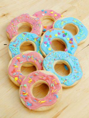 Galletas de mantequilla imitando las rosquillas de los simpson decoradas con glaseado de color rosa y azul y pequeñas virutas de colores