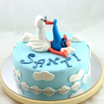 Tarta forrada de fondant azul con nubes de fondant de color blanco, nombre de niño en fondant blanco y en su base una figura de cigüeña y bebe en fondant.