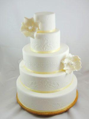 Tarta de cinco pisos cubiertos de fondant blanco y pequeños dibujos en glaseado real, y decorado en el tercer y primer piso con dos flores blancas de fondant.