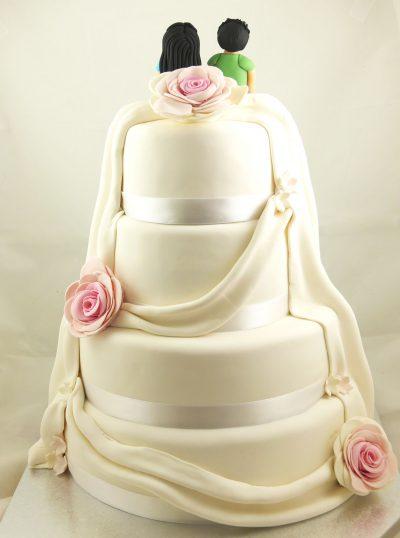 Tarta de cuatro pisos cubierta de fondant blanco cinta de raso alrededor, folres rosas y fondant creando el efecto de tela que cae alrededor.
