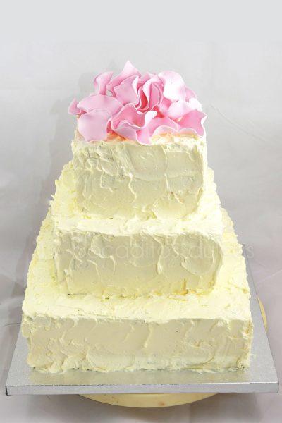 Tarta cuadrada de tres pisos cubierta de buttercream decorada con petalos de rosas modelados en fondant.