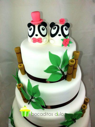 Tarta de cuatro pisos forrados en blanco con una cinta alrededor de raso negro en cada planta decorado con ramas y hojas de fondant y coronada con dos figuritas de osos pandas uno chico vestido de novio y ota de chica.
