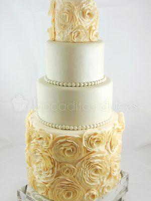 Tarta de cuatro pisos, la de la base y la que corona la tarta decoradas con rosos color crema y la segunda y tercera cubiertas de fondant blanco y alrededor pequeñas perlas blancas en fondant.