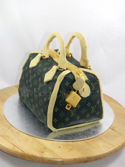Bizcocho circular tallado dandole forma de bolso, este en concreto imita uno de Louise Vuitton.