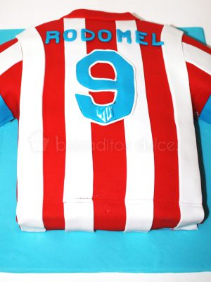 Tarta tallada con forma de camiseta del equipo de futbol del atletico de madrid.