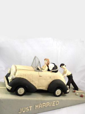 Tarta tallada en forma de coche, con dos novios de fondant, la chica conduciendo el coche y el chico empujandolo.