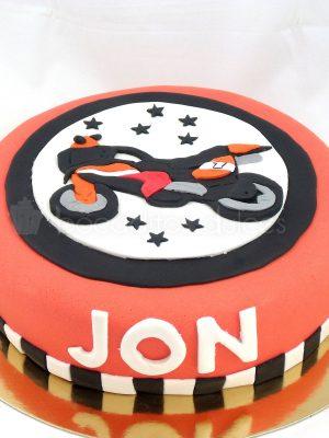 Tarata forrada con fondant rojo, u una cinta de color blanco y negro el nombre de Jon en fondant blanco y una moto modelada en fondanat.